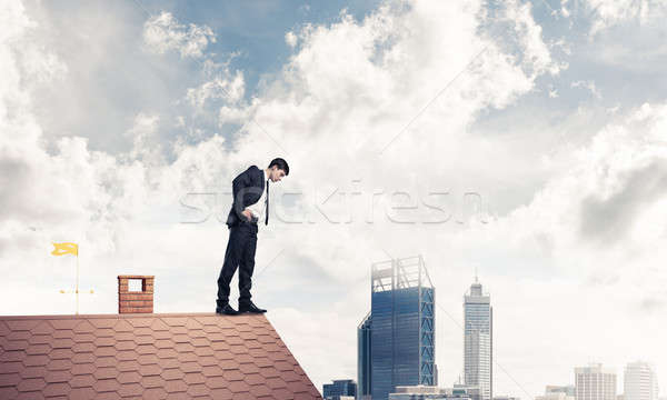 Businessman looking down from roof and afraid to make step. Mixe Stock photo © adam121