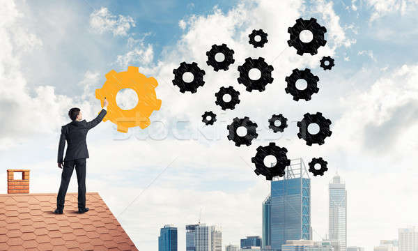 Businessman standing with back on house brick roof and drawing.  Stock photo © adam121