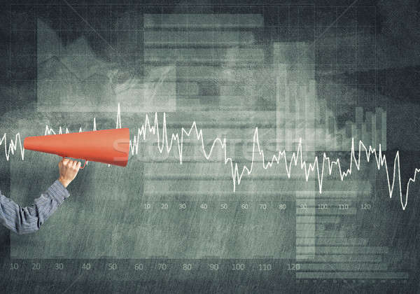 Hand of man holding red paper trumpet against graphs background Stock photo © adam121