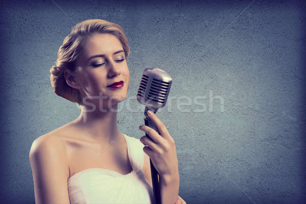 attractive female singer with microphone Stock photo © adam121