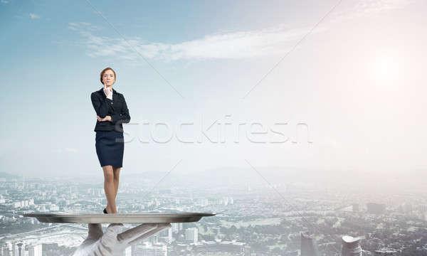 Confident elegant businesswoman presented on metal tray against cityscape background Stock photo © adam121