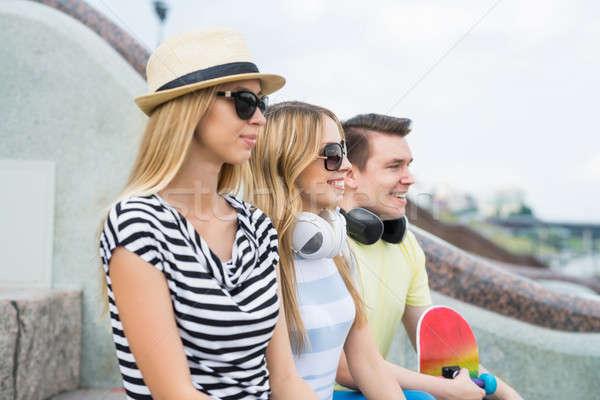 Beztroski summertime trzy młodych szczęśliwych ludzi posiedzenia Zdjęcia stock © adam121