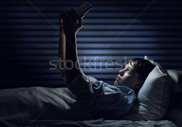 Internet bağımlılık genç erkek yatak Stok fotoğraf © adam121