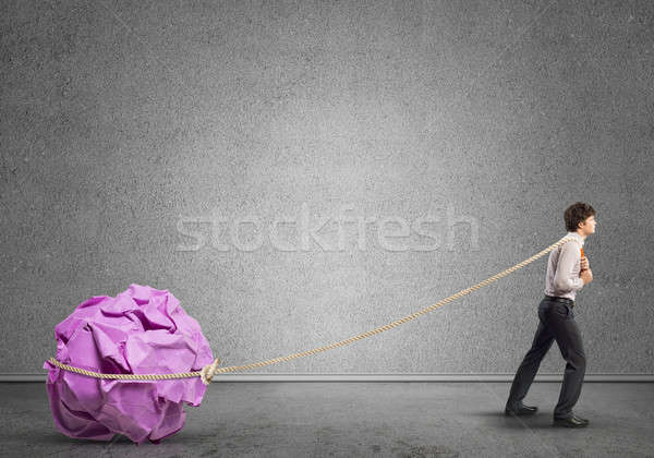 Stock photo: Man pulling with effort big crumpled ball of paper as creativity sign