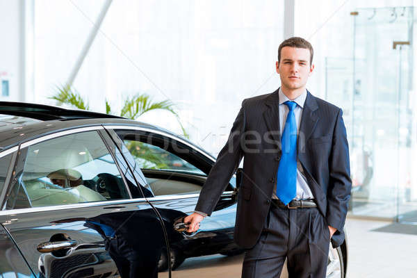dealer stands near a new car in the showroom Stock photo © adam121