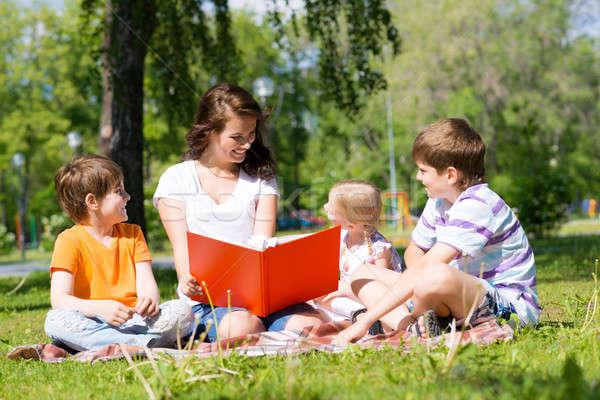 teacher reads a book to children in a summer park Stock photo © adam121