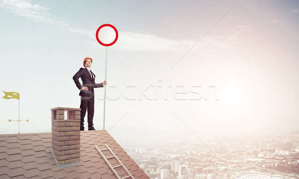 Caucasian businessman on brick house roof showing stop road sign Stock photo © adam121
