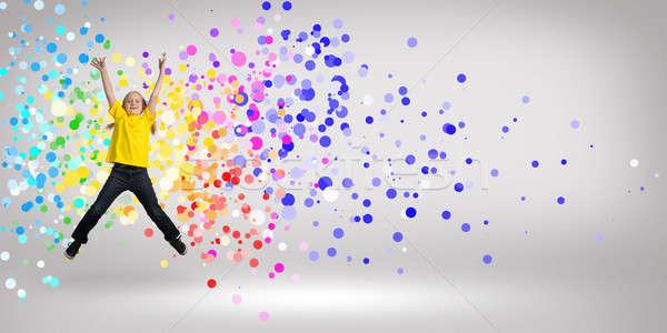 Dziewczyna skoki funny około kolorowy promienie Zdjęcia stock © adam121