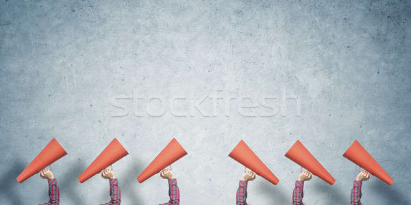 Many hands of woman holding paper trumpet against concrete background Stock photo © adam121