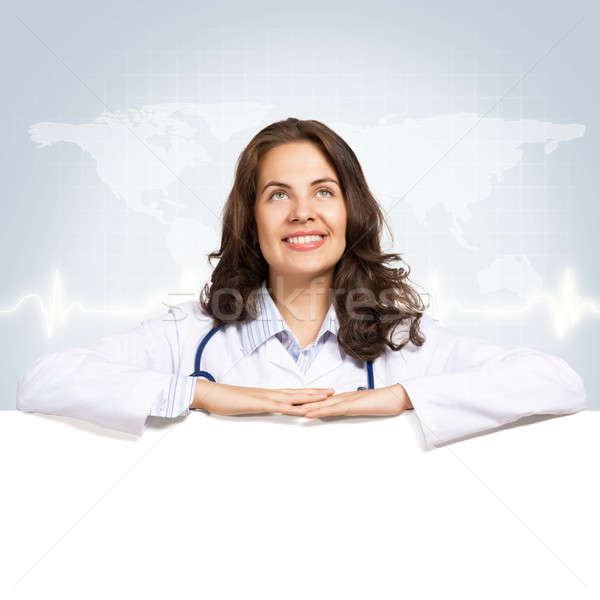 Stock photo: young woman doctor with a blank banner