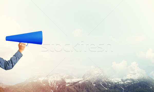 Hand of man holding paper trumpet against natural landscape back Stock photo © adam121