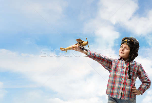 Boy in helmet pilot playing with a toy airplane Stock photo © adam121