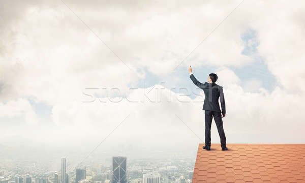Businessman on house roof touch empty space. Mixed media Stock photo © adam121