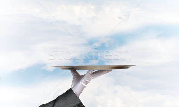 Waiter holding empty silver platter ready for product or item placement Stock photo © adam121