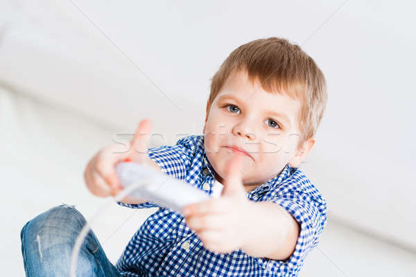 Boy playing on a game console Stock photo © adam121