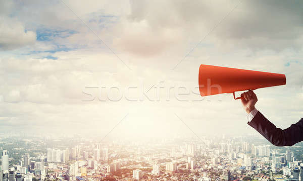 Hand of businesswoman holding red paper trumpet against cityscap Stock photo © adam121