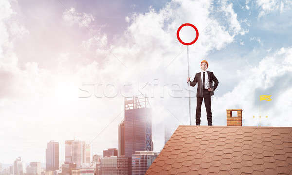 Caucasian businessman on brick house roof showing stop road sign. Mixed media Stock photo © adam121