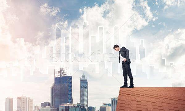 Imprenditore guardando verso il basso tetto moderno cityscape giovani Foto d'archivio © adam121