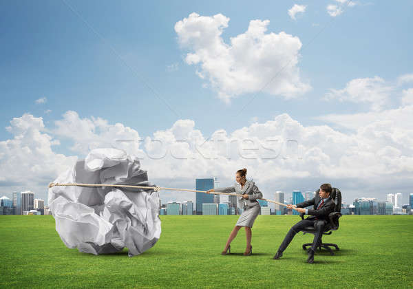 Businesspeople pulling with effort big crumpled ball of paper as creativity sign Stock photo © adam121