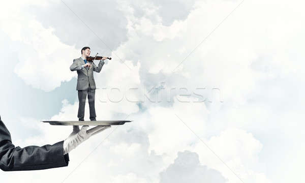 Businessman on metal tray playing violin against blue sky background Stock photo © adam121