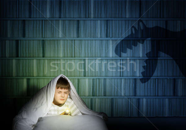 Stock photo: boy under the covers with a flashlight
