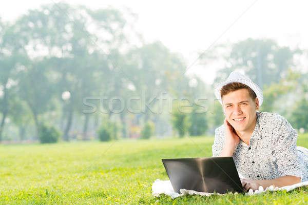 Młody człowiek pracy parku laptop posiedzenia trawy Zdjęcia stock © adam121