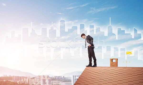 Businessman looking down from roof and modern cityscape at background. Mixed media Stock photo © adam121