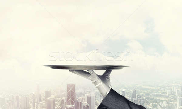 Stock photo: Hand presenting metal empty tray and modern city landscape at ba