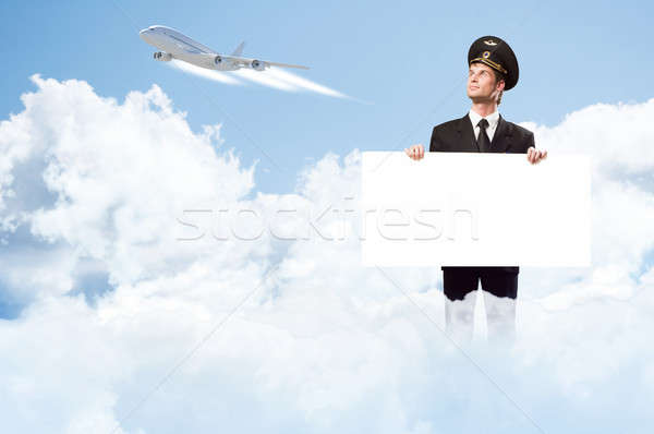 Stock photo: pilot in the form of holding an empty billboard