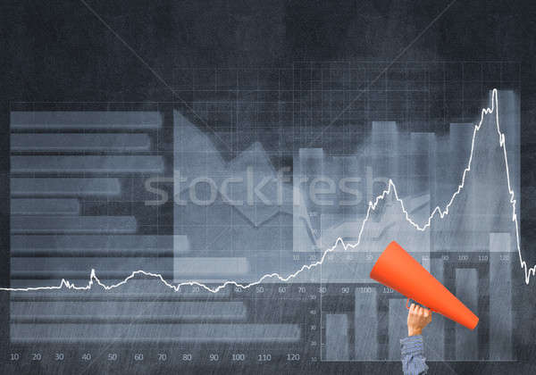 Stock photo: Hand of man holding red paper trumpet against graphs background