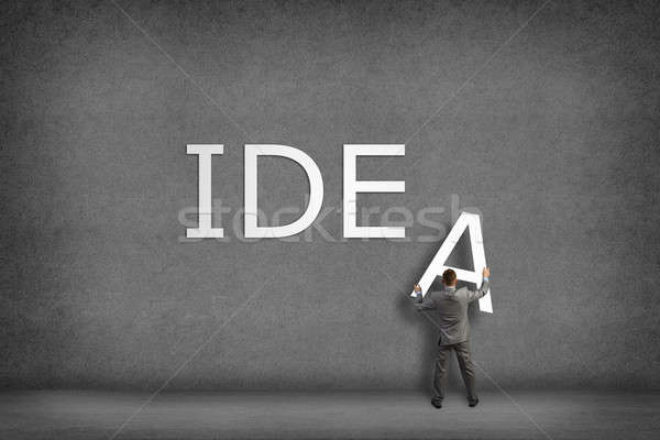 Businessman collects on the wall the word idea Stock photo © adam121