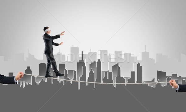 Business concept of risk support and assistance with man balancing on rope Stock photo © adam121
