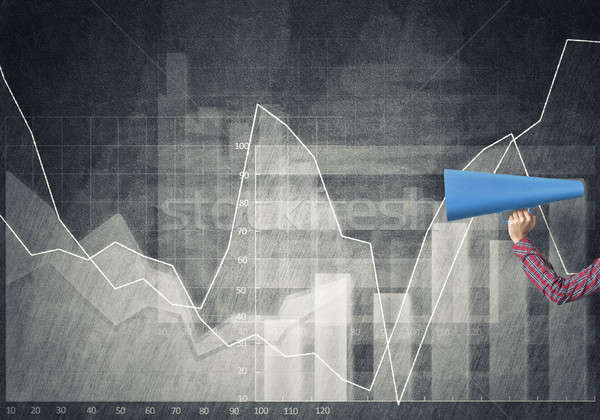 Hand of woman holding blue paper trumpet against graphs backgrou Stock photo © adam121