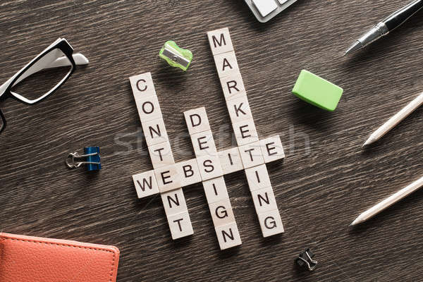 Business workplace with office stuff and wooden cubes making crossword Stock photo © adam121