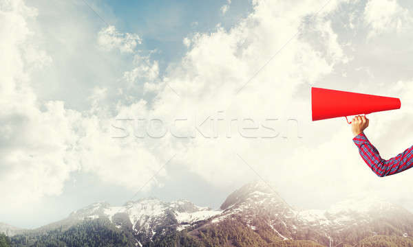 Hand of woman holding paper trumpet against natural landscape ba Stock photo © adam121