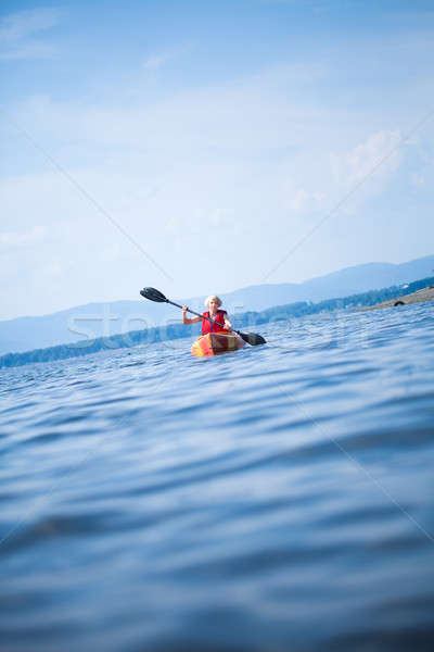 Woman With Safety Vest Kayaking Alone on a Calm Sea Stock photo © aetb
