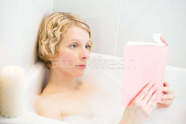 Young woman relaxing in the bath and reading a book Stock photo © aetb