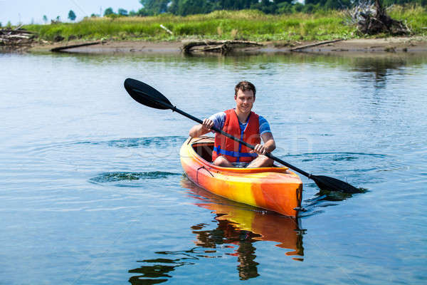 Man With Safety Vest Kayaking Alone on a Calm River Stock photo © aetb
