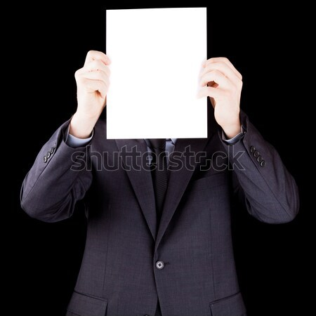 Businessman holding  a sheet of paper in front of his face Stock photo © aetb
