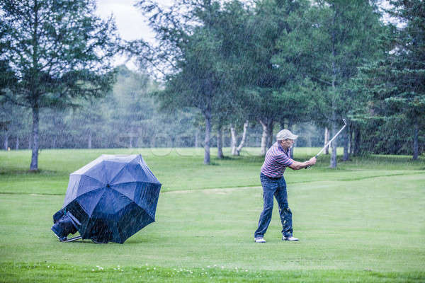 Golfer on a Rainy Day Swigning in the Fairway Stock photo © aetb