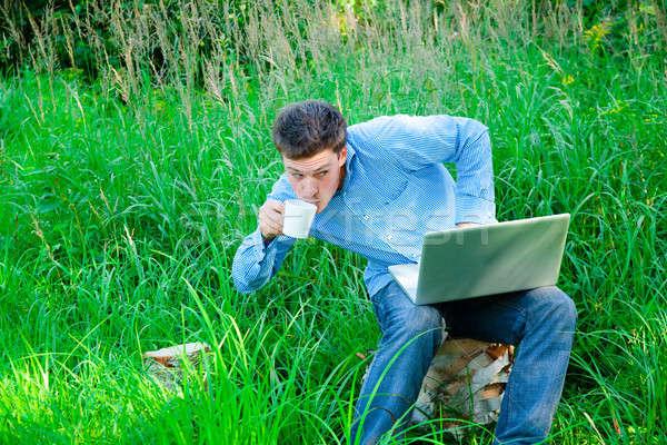 Jonge man buitenshuis beker laptop man iets Stockfoto © aetb