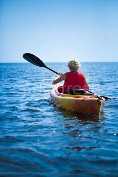Woman Wearing a Safety Vest Heading out to sea Alone  Stock photo © aetb