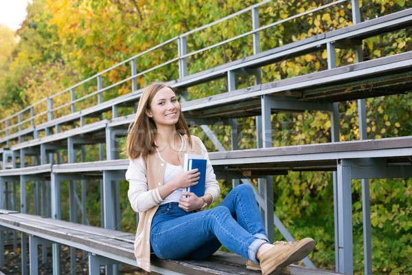 Estudiante sesión deporte libro sonriendo cámara Foto stock © Agatalina