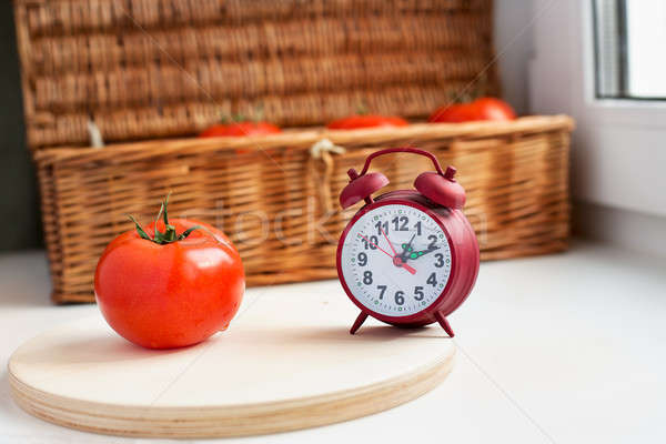 One tomato and red clock Stock photo © Agatalina
