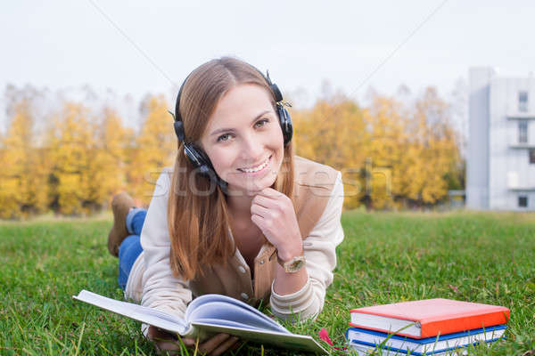 Student listening to headphones and holding opened book Stock photo © Agatalina
