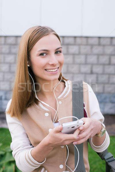 студент прослушивании телефон наушники улыбаясь камеры Сток-фото © Agatalina