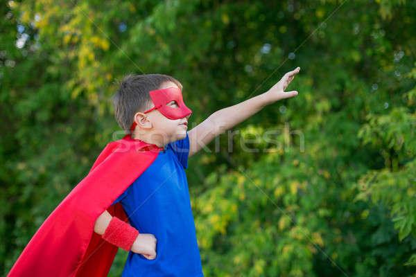 Superhero standing sideways and calling on forward Stock photo © Agatalina