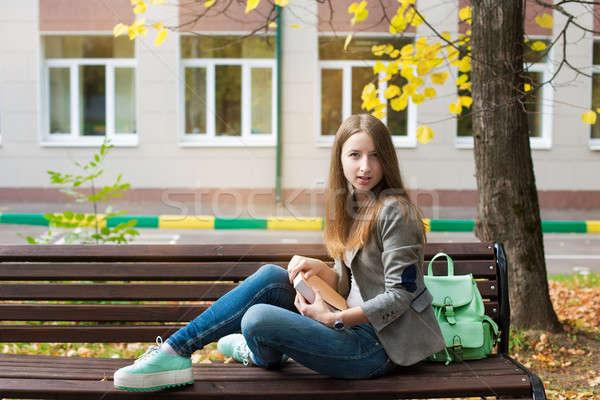 Student posiedzenia ławce książki patrząc kamery Zdjęcia stock © Agatalina