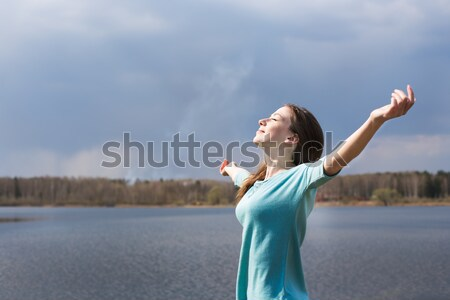 Freckled happy girl with closed eyes smiling to sun Stock photo © Agatalina