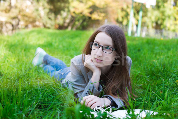 Student with glasses lying on grass  Stock photo © Agatalina